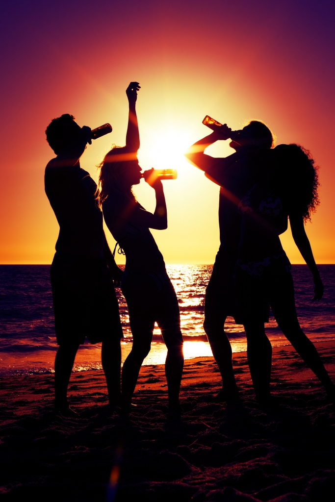 20932984 - people (two couples) on the beach having a party, drinking and having a lot of fun in the sunset (only silhouette of people to be seen, people having bottles in their hands with the sun shining through)