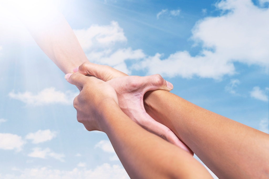 Helping hand, male hand takes young female hand on blue sky