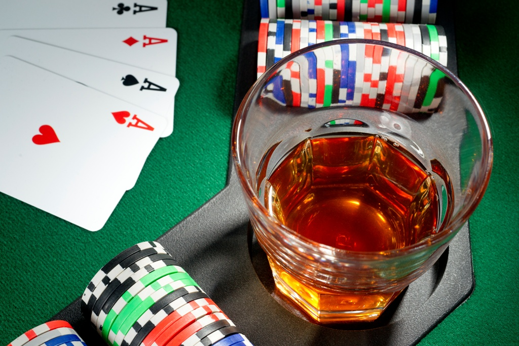 Four aces, glass of whiskey and chips on a poker table