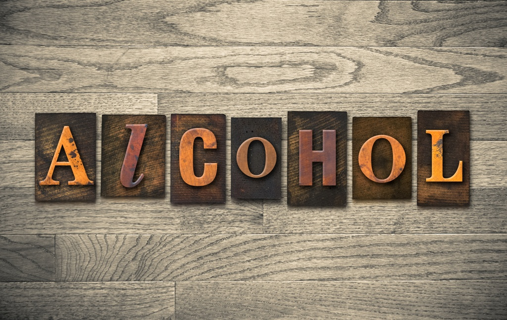 """The word """"ALCOHOL"""" theme written in vintage, ink stained, wooden letterpress type on a wood grained background."""
