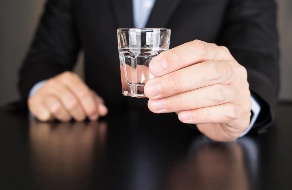 Businessman holding glass of vodka