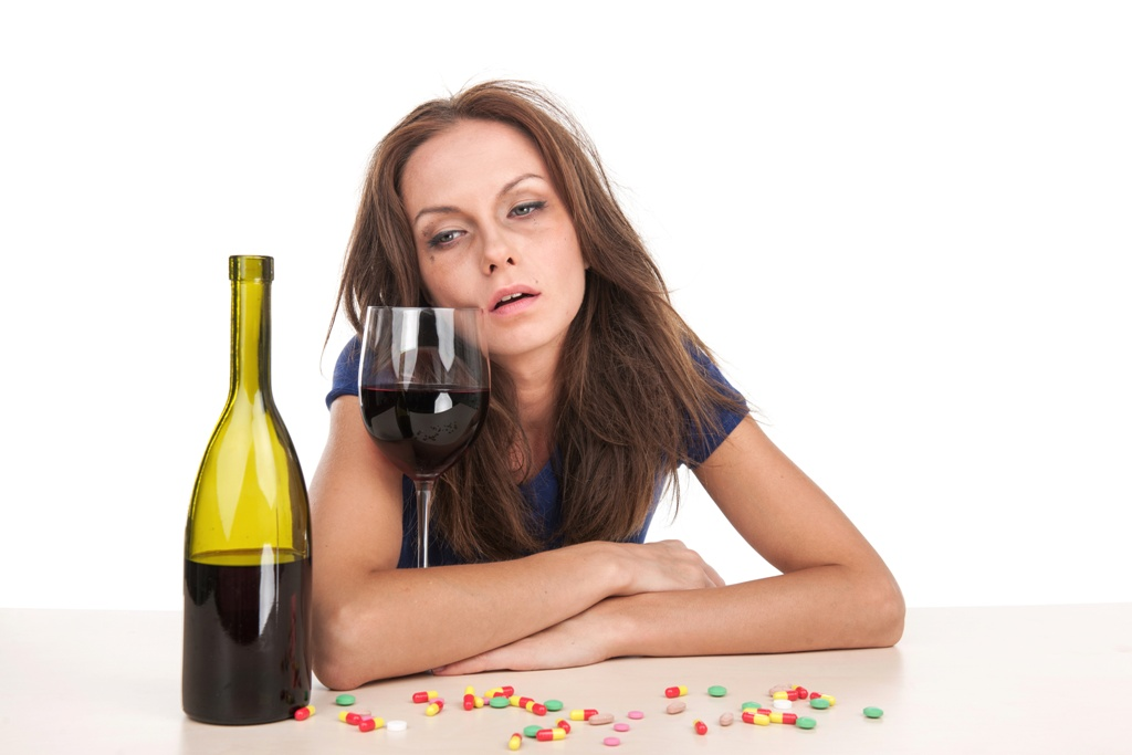 Pills lying on table with bottle of wine on white background. woman suffering from pain and headache