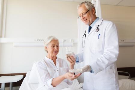 48902673 - doctor giving medication and water to senior woman at hospital ward