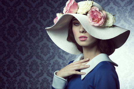 38253095 - elegant pretty woman in blue dress with a spring white hat , with pink and white roses over .
