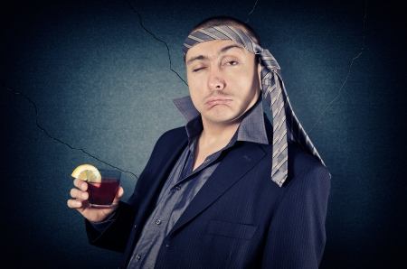 18518258 - drunk businessman with tie on his head and a glass in her hand